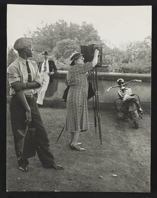 [Photographer Frances Benjamin Johnston standing beside her view camera preparing to take a photograph Biltmore Estate; her assistant Huntley Ruff is in the foreground and a motorbike is in the background]
