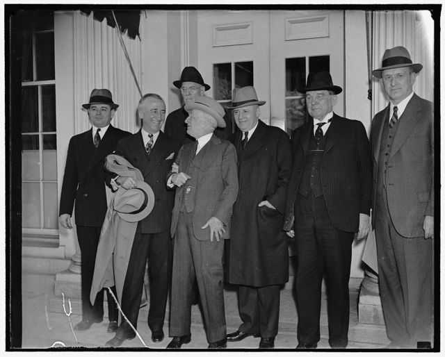 President organizes $4,000,000,000 pump priming campaign. Washington, D.C., April 11. President Roosevelt met with his Relief and Congressional Aides today to the personal command of a new administration fight to check business recession with a $4,000,000,000 pump priming campaign. The president subordinated all other White House business to efforts to hammer his lending and spending program into shape as a major New Deal offensive against recession and unemployment, left to right: Director of the Budget Daniel Bell, Sen. James F. Byrnes, SC. Sen. Carter Glass of Va., Majority Leader of the House Sen. Sam Rayburn of Tex., Sen Kenneth McKeller of Tenn., Sec. of Treasury Henry Morenthau, and in the rear, Rep. Edward Johnson, of Colo., April 11, 1938