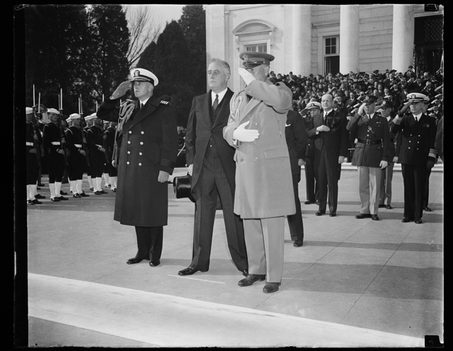 PRESIDENT PAYS HOMAGE TO AMERICA'S UNKNOWN SOLDIER ON ARMISTICE DAY. WASHINGTON, D.C. NOVEMBER 11. HEAD UNCOVERED, PRESIDENT ROOSEVELT STANDS IN SILENT PRAYER AFTER PLACING A WREATH ON THE TOMB OF THE UNKNOWN SOLDIER TO LEAD THE NATION IN OBSERVING ARMISTICE DAY. WITH THE CHIEF EXECUTIVE ARE HIS NAVAL AND MILITARY AIDES CAPT. DANIEL J. CALLAGHAN, LEFT, AND COL. EDWIN M. WATSON