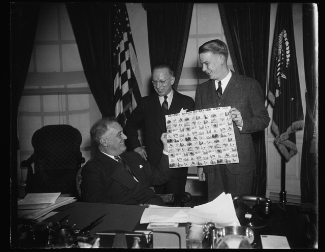 PRESIDENT RECEIVES WILD LIFE STAMPS. WASHINGTON, D.C. FEBRUARY 24. PRESIDENT ROOSEVELT TODAY ADDED FURTHER TO HIS STAMP COLLECTION WHEN HE WAS PRESENTED WITH A BLOCK OF WILD LIFE STAMPS IN COMMEMORATION OF WILD LIFE RESTORATION WEEK. IN THE PHOTOGRAPH, L TO R: PRESIDENT ROOSEVELT; FRED F. JORDAN, DIRECTOR OF WILD LIFE RESTORATION WEEK; AND MINOR HUDSON, U.S. JUNIOR CHAMBER OF COMMERCE