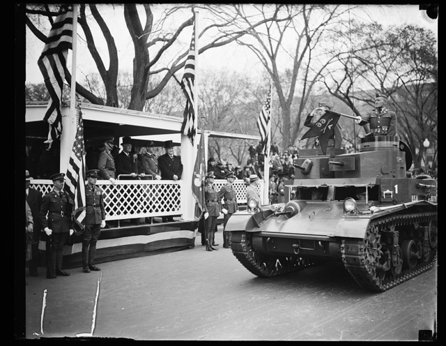 PRESIDENT ROOSEVELT REVIEWS ARMY DAY PARADE. WASHINGTON, D.C. APRIL 6. PRESIDENT ROOSEVELT LED THE NATION TODAY IN OBSERVING ARMY DAY AS HE REVIEWED A COLORFUL PARADE COMPRISED OF VIRTUALLY EVERY ARM OF THE SERVICE. RUMBLING OF THE GIANT TANKS REVIVED MEMORIES OF AMERICA'S ENTRY INTO THE WORLD WAR TWENTY-ONE YEARS AGO TODAY. IN THE STAND CAN BE SEEN, L TO R: BRIG. GEN. WILLIAM F. BRYDEN, GRAND MARSHAL OF THE PARADE; PRESIDENT ROOSEVELT; BRIG. GEN. ALBERT COX OF THE D.C. NATIONAL GUARD; AND ASSISTANT SECRETARY OF WAR LOUIS JOHNSON