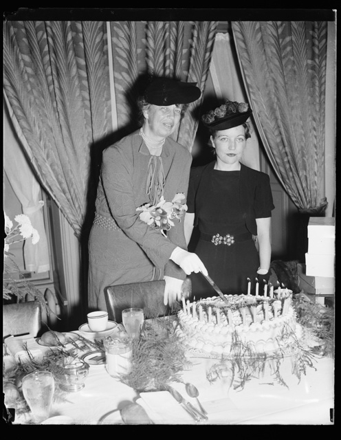 PRESS WOMEN FETE MRS. ROOSEVELT ON 54TH BIRTHDAY. WASHINGTON, D.C.OCTOBER 11. CELEBRATING HER 54TH BIRTHDAY TODAY, MRS. FRANKLIN D. ROOSEVELT WAS ENTERTAINED AT A SPECIAL LUNCHEON IN HER HONOR BY MEMBERS OF THE WOMEN'S NATIONAL PRESS CLUB. THE FIRST LADY IS PICTURED CUTTING HER BIRTHDAY CAKE, WHICH INCIDENTLY CONTAINEDONLY 21 CANDLES. MISS HOPE RIDINGS MILLER, PRESIDENT OF THE CLUB, IS ON THE LEFT