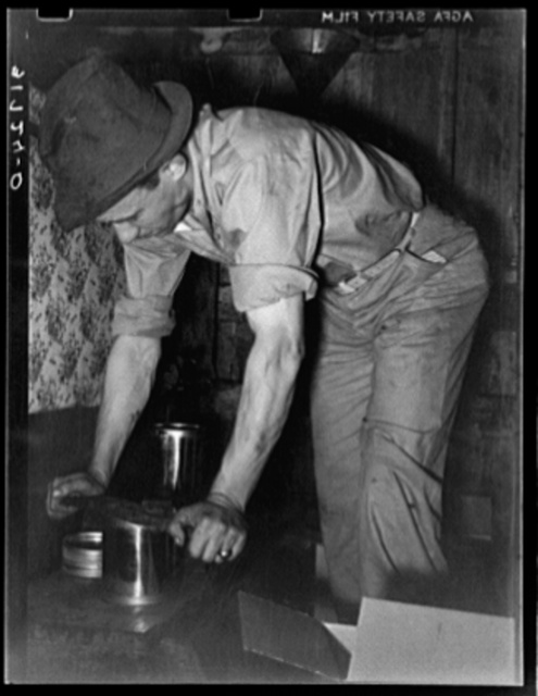 Pressing top onto tin can full of syrup. Syrup mill near New Iberia, Louisiana