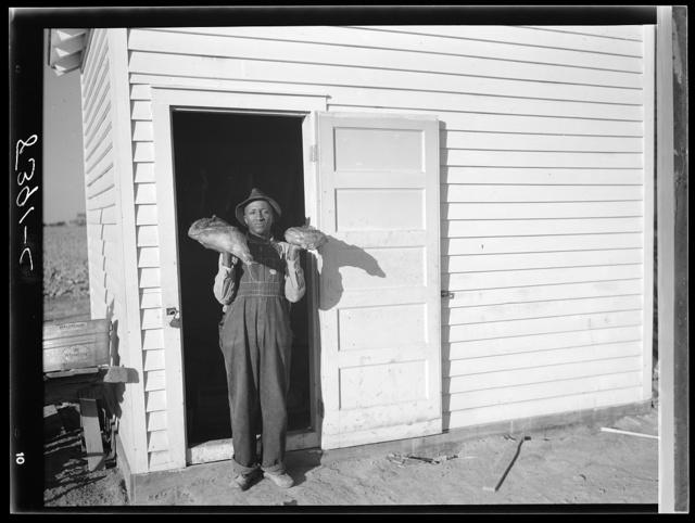 Project farmer in front of smokehouse. Roanoke Farms, North Carolina