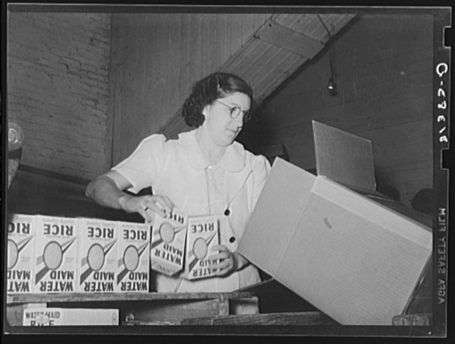 Removing packages of rice from conveyer to place them in fiber cartons.  State rice mill, Abbeville, Louisiana