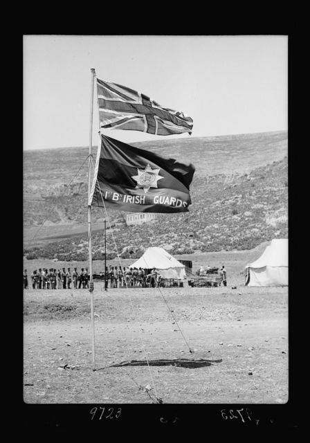 Result of terrorist acts & government measures. Camp of First Irish Guards at foot of Ebal, close-up of flags, British & regimental