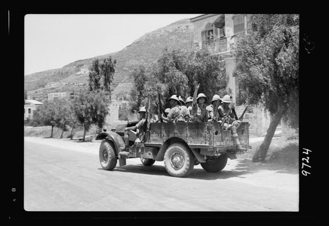 Result of terrorist acts & government measures. Irish Guard troops on outskirts of Nablus leaving camp to fight the gangs on hills