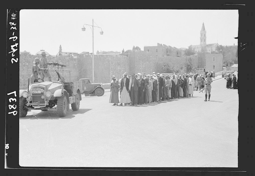 Search for arms en masse outside Damascus Gate, Sept. 9, '38. Citizens covered with machine-gun while being searched. Large group in foreground being under temporary arrest