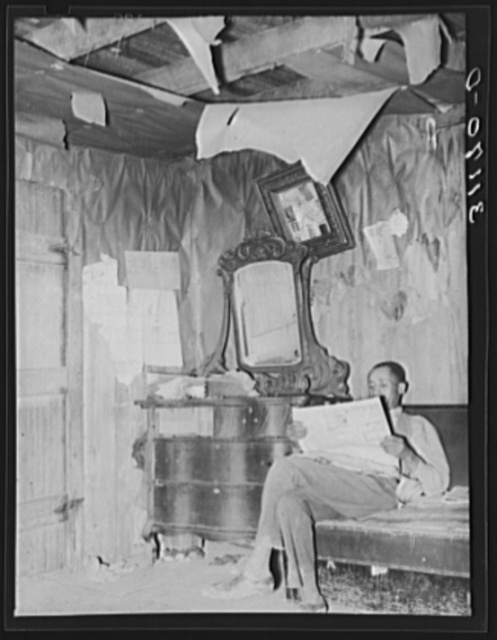 Sharecropper reading newspaper in corner of living room. Note the bureau and ceiling. Near Southeast Missouri Farms