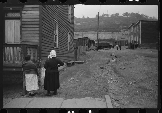Shenandoah(?), Pennsylvania. Two women talking outside a house at the end of a street, watching some neighbors and the unloading of a truck on a drab-looking side street