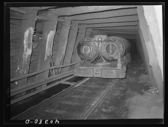 Shenandoah (vicinity), Pennsylvania. A compressed air engine approaching with a train of cars in the Maple Hill mine. The pipes beside the track carry eight hundred pounds and there are valves for refueling every quarter mile. Compressed air is piped down from the surface