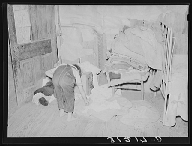 Southeast Missouri Farms. Child picking up clothes in corner of bedroom of shack home. Note lack of storage facilities