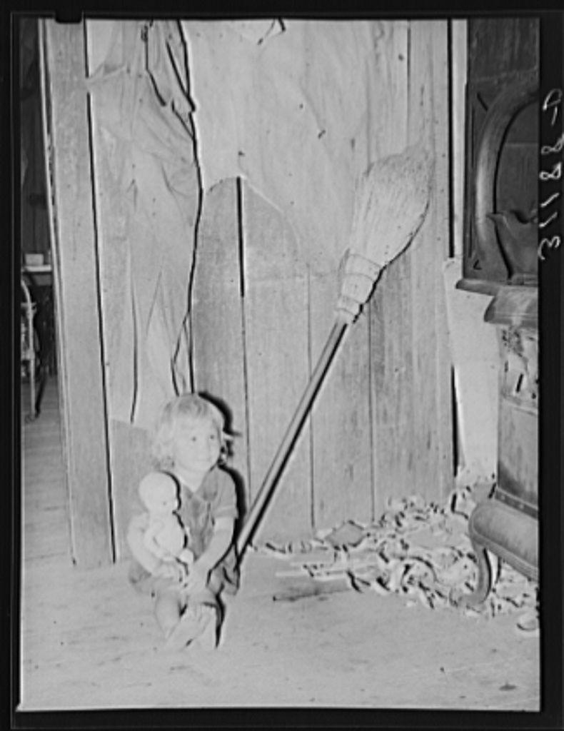 Southeast Missouri Farms. Daughter of sharecropper with doll on kitchen in shack home