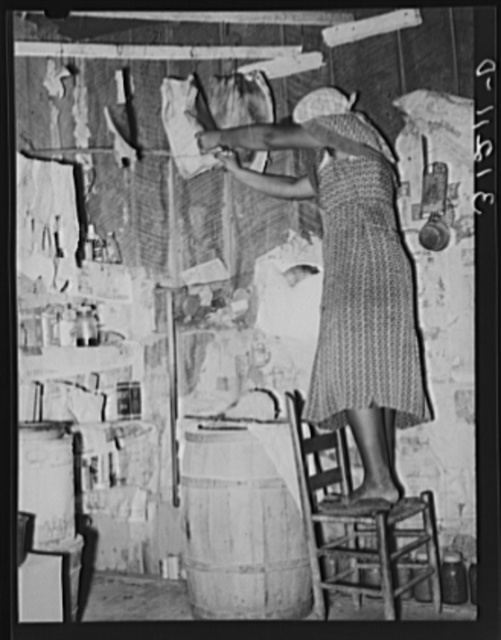 Southeast Missouri Farms. Sharecropper's wife cutting off piece of fatback from slab in kitchen