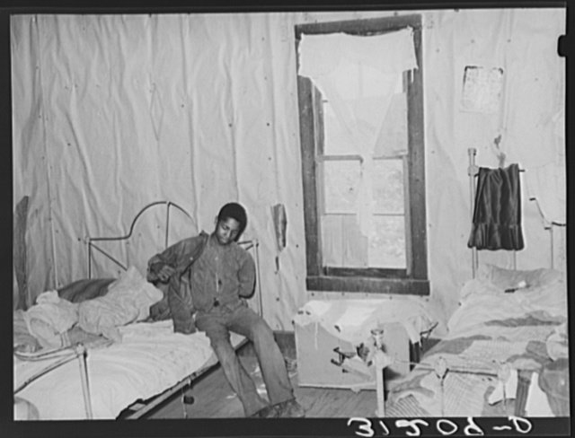 Southeast Missouri Farms. Son of sharecropper getting dressed in bedroom shack