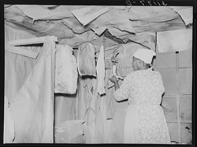 Southeast Missouri Farms. Wife of sharecropper cutting piece of fatback from slab in kitchen of shack home