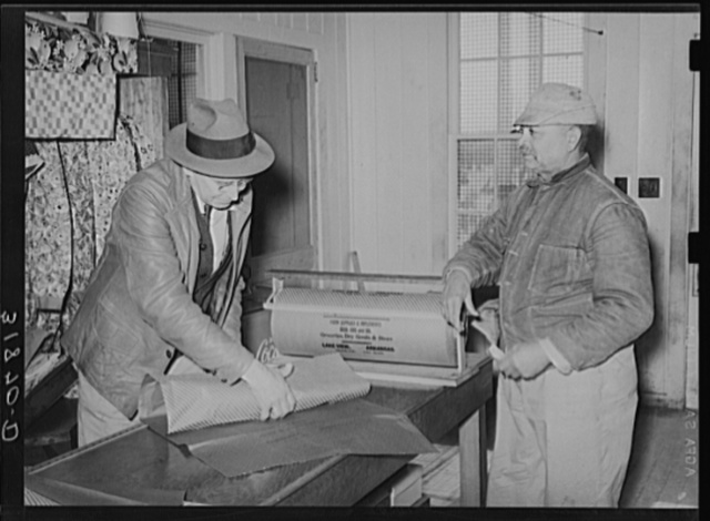 Storekeeper wrapping up package for farmer. Lakeview Project, Arkansas