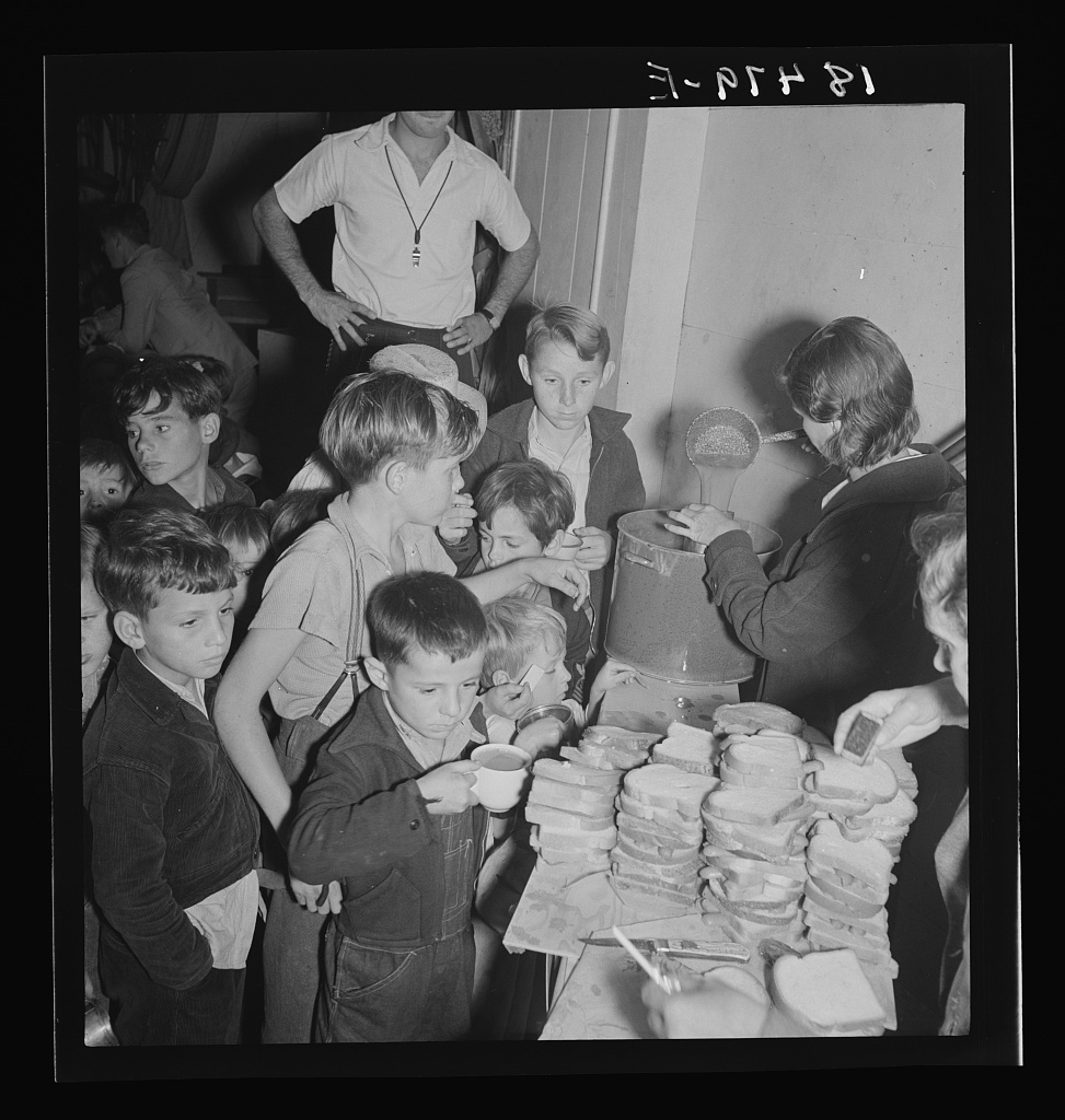 The children crowd and push to reach the refreshments at Halloween party in Shafter migrant cooperative. California