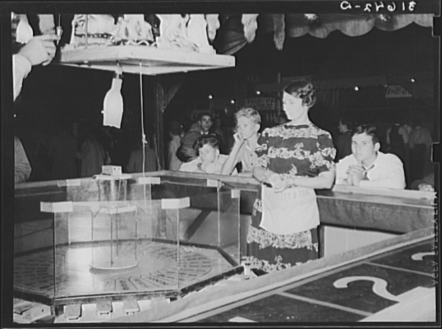 The new gambling game: Where will the mouse run? A concession at South Louisiana State Fair, Donaldsonville, Louisiana. Players place bets on particular numbers, caged mouse is placed on top of central cylinder, trap door is released and mouse runs to a numbered hole