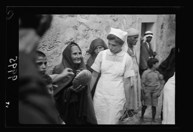 The raising of the siege of Jerusalem. An old familiar figure of the neighborhood receiving her loaf from on of the nurses of the Anna Spafford Baby House