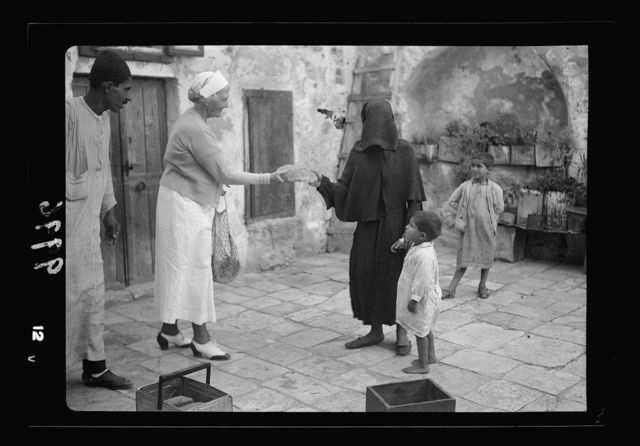 The raising of the siege of Jerusalem. Scene in the courtyard of a poor Moslem [i.e., Muslim] Home, showing Mrs. F. Vester, president of the American Colony Aid Association, handing out a loaf of bread to the veiled Moslem woman & her 2 little boys