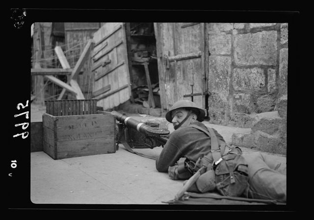 The raising of the siege of Jerusalem. Typical scene of troops in Old City before the lifting of curfew. Close-up of machine-gunner lying on his stomach on Bab-el-Silseleh Street with gun pointed toward the entrance of the Mosque grounds