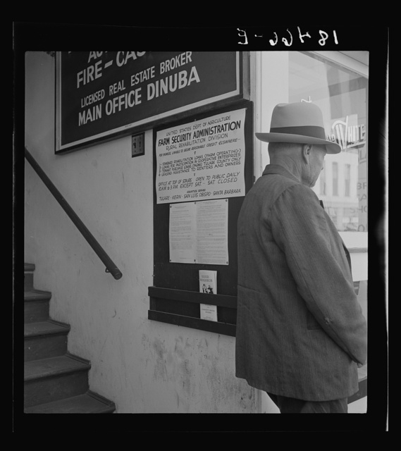 The street entrance to the Farm Security Administration office, Visalia, Tulare County, California. This farmer has come into town to discuss problems with the rural rehabilitation supervisor