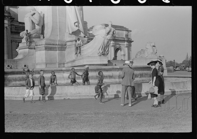 Tourists arriving at Washington, D.C. Throwing pennies to colored boys in fountain across from Union Station