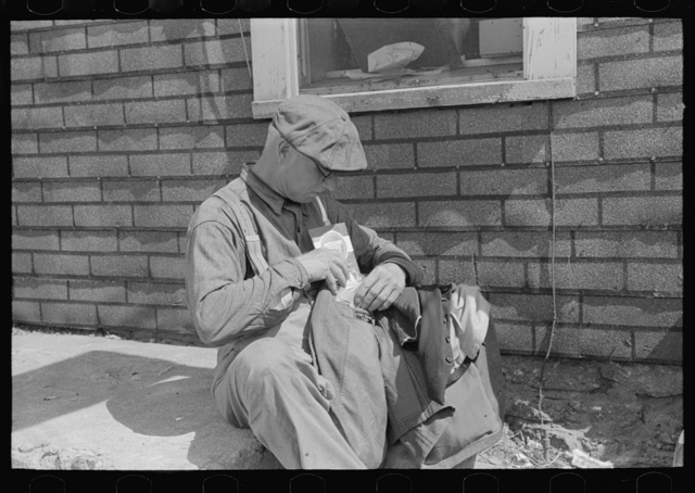 Transient putting timetable into coat pocket. Note that label of coat reads New York. Sikeston, Missouri
