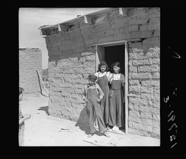 """Two sisters and brother before their house. Great Western Sugar Company's beet sugar workers' colony at Hudson, Colorado. The father is dead, and the girls don't attend school because they're """"too old,"""" and the boy because he is """"sick all the time"""""""