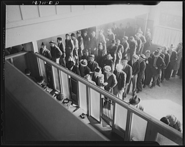 Unemployment benefits aid begins. Line of men inside a division office of the State Employment Service office at San Francisco, California, waiting to register for benefits on one of the first days the office was open. They will receive from six to fifteen dollars per week for up to sixteen weeks. Coincidental with the announcement that the federal unemployment census showed close to ten million persons out of work, twenty-two states begin paying unemployment compensation