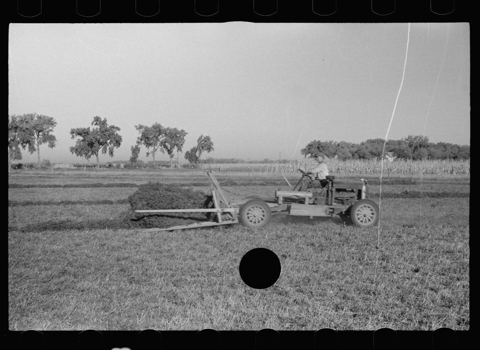Untitled photo, possibly related to: Using a power rake on the alfalfa fields of Dawson County, Nebraska. Dawson County is the greatest alfalfa producing center in the world