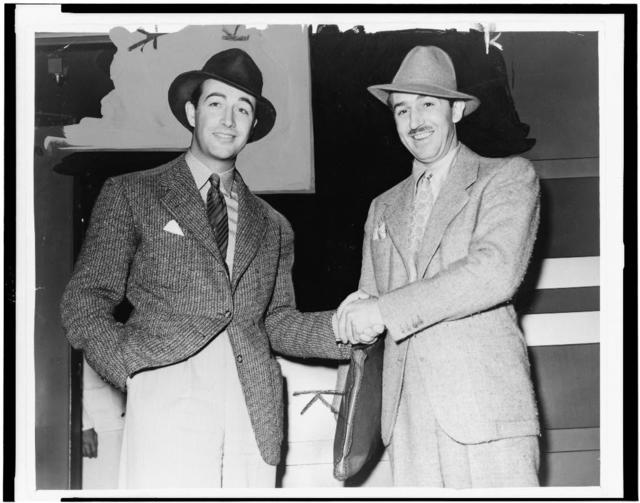 [Walt Disney shakes hands with Robert Taylor, three-quarter length portraits] / World-Telegram photo by Alan Fisher.
