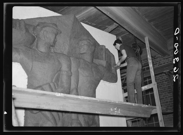 Washington, D.C. Vernon Atchely of the Special Skills division of the U.S. Resettlement Administration working on figures modeled in relief for the Greendale school