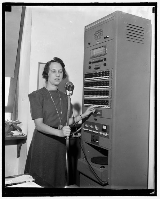 [Woman at microphone stand adjusting levers on a large console with Triplett Meter Company decibel display]