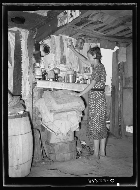 Woman living in shack at Tin Town, Caruthersville, Missouri, in front of shelf used as kitchen cabinet. Note ceiling and dirt floor