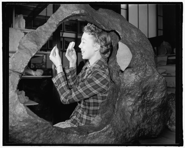 [Woman posing with the Tucson Ring meteorite at the Smithsonian Museum of Natural History, Washington, D.C.]