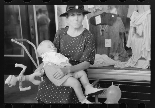 Woman with child in front of store during National Rice Festival, Crowley, Louisiana