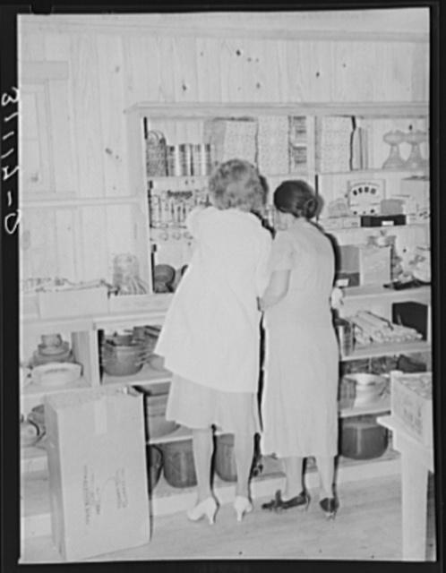Women examining stock of goods. Co-op store. Southeast Missouri farms, Missouri