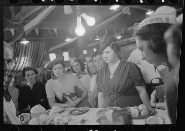 Women watching accomplishments of vegetable shredder at display, state fair, Donaldsonville, Louisiana