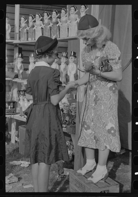 Young girl buying doll from concession manager, state fair, Donaldsonville, Louisiana