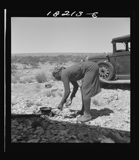 "Young Negro wife cooking breakfast, outskirts of El Paso, Texas. ""Do you suppose I'd be out on the highway cooking my steak if I had it good at home?"" Occupations: hotel maid, cook, laundress"