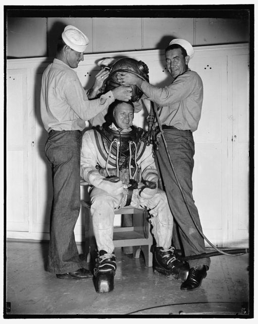 Add record depth reached by Navy divers. William Badders, Master Diver, U.S.N., who recently made a record dive of over 500 feet, is helped into his underwater suit just before taking an experimental dive in the tank at Washington Navy Yard, 8/9/38