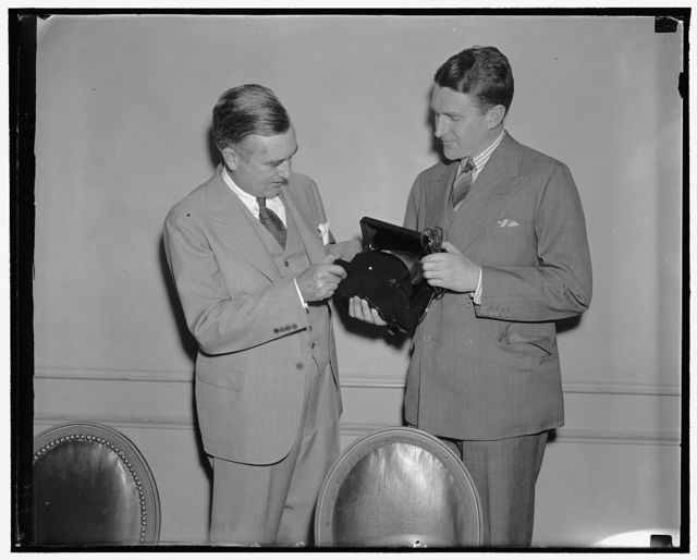 Edison receives first anti-glare lamp. Washington, D.C., May 17. Charles Edison, Asst. Sec. of the Navy and son of the late Thomas A. Edison, left; was presented with the first Polaroid lighting unit, a lamp free from glaring reflection. The lamp, praised by scientists as heralding a great advance in artificial illumination, employs the regulation incandescent light source as perfeted by Thomas A. Edison but passes the light through a sheet of the new light controlling material, Polaroid, to remove the light waves responsible for refelcted glare, one of the worst visual hazards of illumination, George W. Wheelwright, 3rd. who helped in the development made the presentation, 5/14/38
