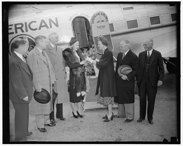 "Hollywood star arrives to participate in celebration of National Airmail Week. Washington, D.C., May 15. A typical Hollywood reception was accorded Miss Marion Weldon, Paramount starlet, as she arrived in Washington today to represent the movie city in participating in National Airmail Week. Miss Weldon will appear in the forthcoming Paramount Technicolor Production ""Men With Wings"" shortly to be released. She was chosen for the honor of representing Hollywood during National Airmail by the 22 pilots and stunt men who are in the production with her. Miss Jean O'Connell, daughter of Ambrose O'Connell, Executive Assistant to the Postmaster General, is pictured presenting a bouquet of flowers to the star. Others in the picture are, left to right: Charles W. Stark, U.S. Chamber of Commerce; Harlee Branch, Asst. Postmaster General; Senaotr William Gibbs McAdoo of California; Ambrose O'Connell, and Walter Hartley, U.S. Chamber of Commerce, 5/15/38"