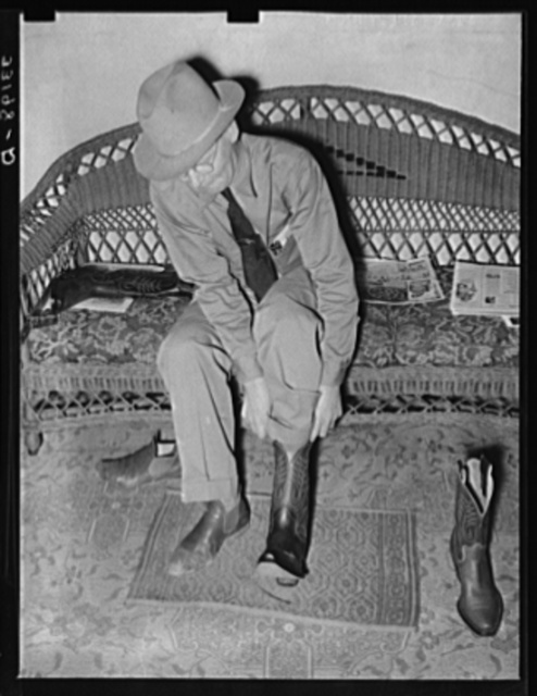 A customer trying on a pair of boots in bootmaking shop. Alpine, Texas