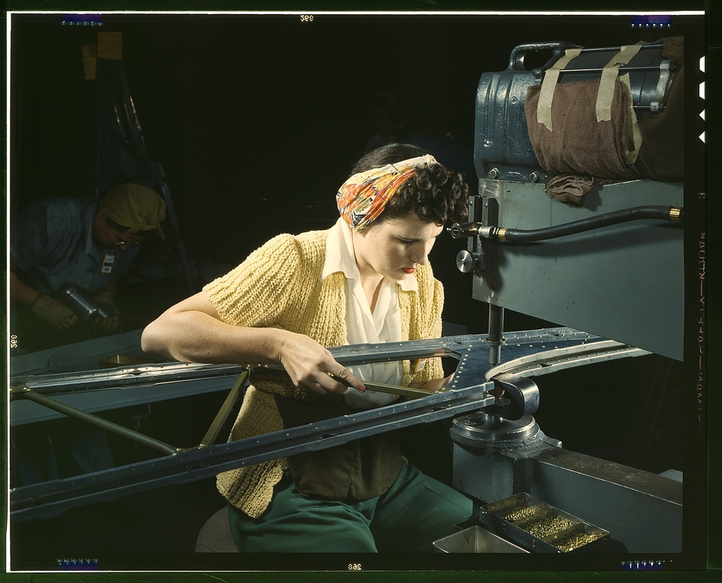"""A girl riveting machine operator at the Douglas Aircraft Company plant joins sections of wing ribs to reinforce the inner wing assemblies of B-17F heavy bombers, Long Beach, Calif. Better known as the """"Flying Fortress,"""" the B-17F bomber is a later model of the B-17, which distinguished itself in action in the south Pacific, over Germany and elsewhere. It is a long range, high altitude, heavy bomber, with a crew of seven to nine men -- and with armament sufficient to defend itself on daylight missions"""