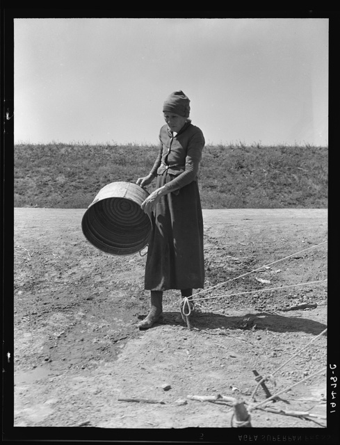 """A grandmother in a migrant camp. Stanislaus County, California. """"Been in California fourteen months. From Oklahoma. The main thing is to get our families located and quieted down. Ain't no use to send them back; it's a waste of money. They won't stay."""""""