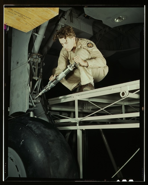 A hydraulic mechanic greasing the landing gear of a transport, before the plane leaves the last station on the assembly line at the Consolidated Aircraft Corporation plant, Fort Worth, Texas