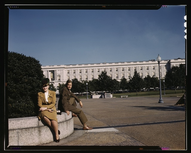 A soldier and a woman in a park, with the Old [Russell] Senate Office Building behind them, Washington, D.C.